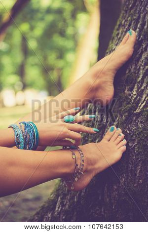 barefoot female feet and hand with boho style bracelets and ring, lean on tree, closeup, selective focus