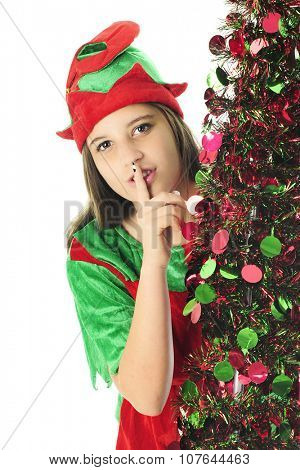 A pretty teen elf peeking around a sparkly Christmas tree with her finger to her lips, saying shh.  On a white background.