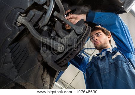 Low angle view of male mechanic repairing car in automobile shop