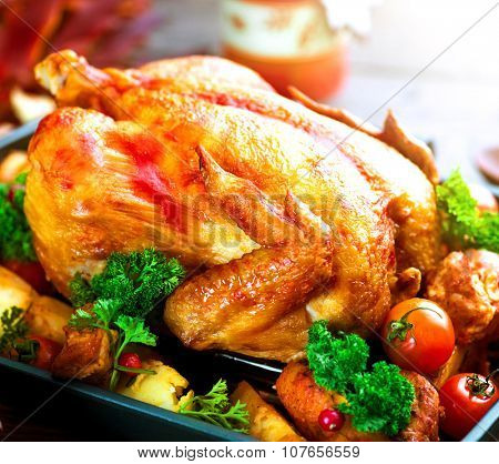 Roasted Chicken. Roasted turkey garnished with Potato, Vegetables and cranberries on a rustic style table decorated with autumn leaves and candles. Thanksgiving Dinner