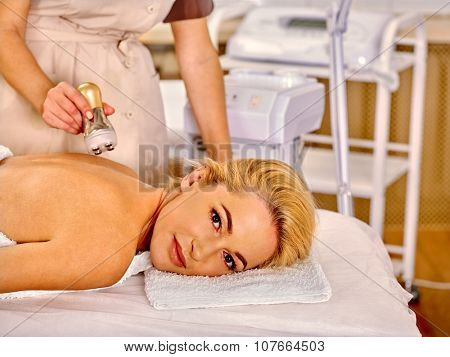 Young woman receiving electrophoresis back body massage  at beauty salon.