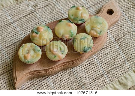 Seven muffins with salmon, spinach and cheese on wood cutting board