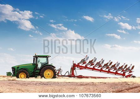 Agriculture Plowing Tractor On Wheat Cereal Field