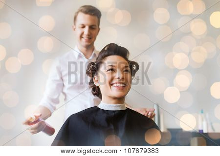 beauty, hairstyle and people concept - happy young woman with hairdresser with hair spray fixating hairdo at salon over holidays lights poster