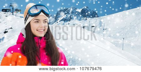winter, leisure, sport and people concept - happy young woman in ski goggles over snow and mountain background poster