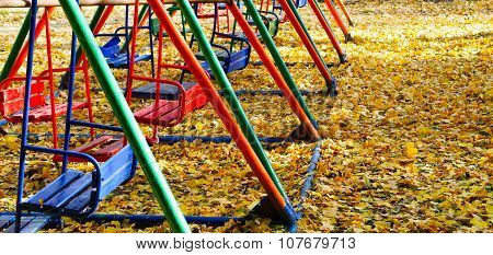 Several Children's Swing In Autumn Park