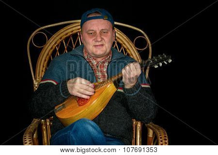 Portrait of mature man sitting in wicker chair and playing mandolin