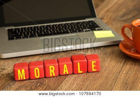 Morale written on a wooden cube in a office desk