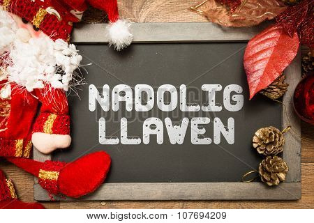Blackboard with the text: Happy Christmas (in Welsh) in a conceptual image poster