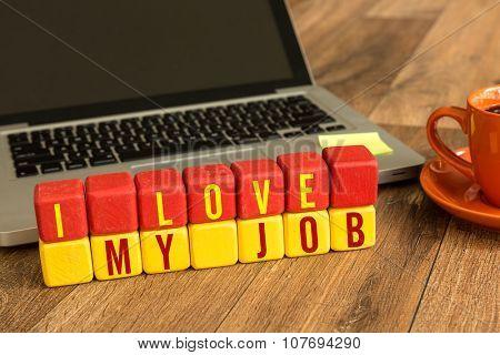 I Love My Job written on a wooden cube in a office desk