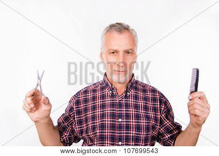Confident Aged Man Choosing Between Scissors And Comb