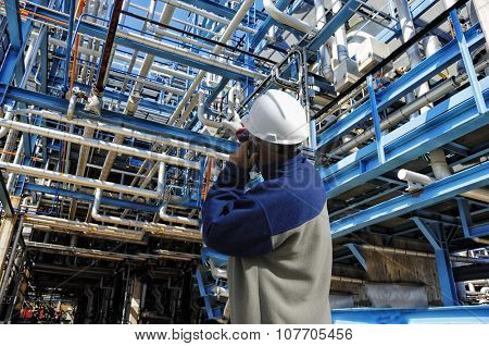 oil and gas worker inside large pipelines constructions inside refinery industry