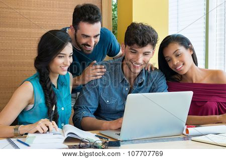 Closeup of young man and woman looking at laptop. Happy smiling students using laptop fot studying. Happy young friends using computer and smiling.