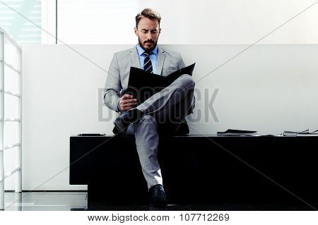 Confident man entrepreneur studying important paper documents before business meeting