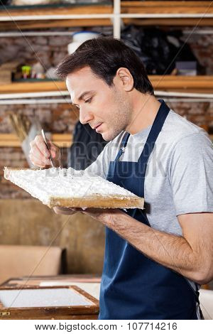 Mid adult worker removing dirt from paper in factory poster