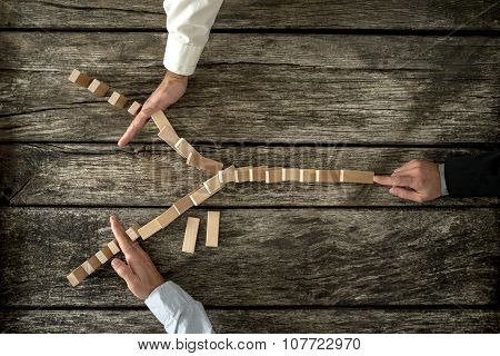 Top view of male hand pushing dominos placed in Y shape knocking them down and two other hands stopping them each on one side. Conceptual of crisis management in business. poster