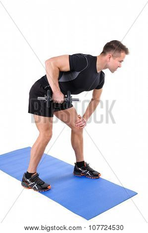 Young man shows starting position of Standing Tricep Dumbbell Kickback workout, isolated on white