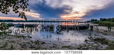 Panormic Landscape With Boats On The Water Near The Old Pier. Beautiful View Of Colorful Sunset On T