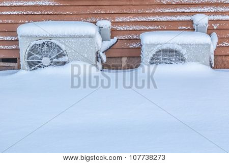 Two residential heat pumps buried in snow.