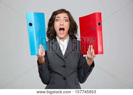 Crazy hysterical pretty curly young woman in gray jacket screaming and holding blue and red binders