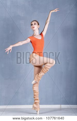 Slender Ballerina Rehearsing In A Dance Movement. On One Foot On Tiptoe.