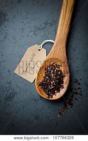 Chipotle chili flakes on a wooden spoon