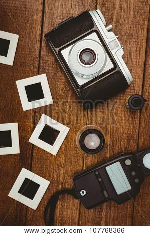 View of an old camera with photos slides on wood desk