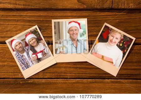 Instant photos on wooden floor against festive couple holding christmas gifts