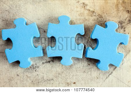 Three Puzzle Pieces On Old Canvas