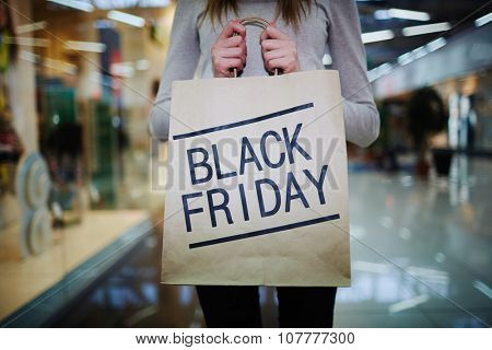 Young shopper showing Black Friday paperbag in the mall