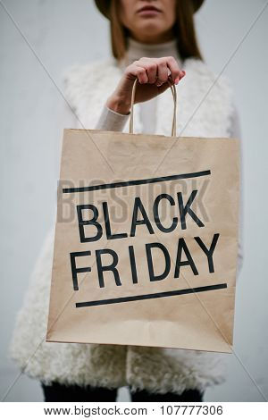 Young woman showing Black Friday paperbag