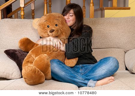 Young Woman Embracing Teddy Bear Sitting On Sofa