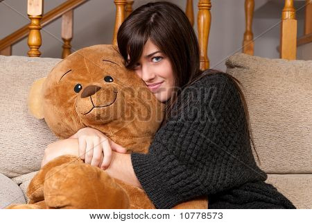 Young Woman Embracing Teddy Bear Sitting On Sofa Close-up