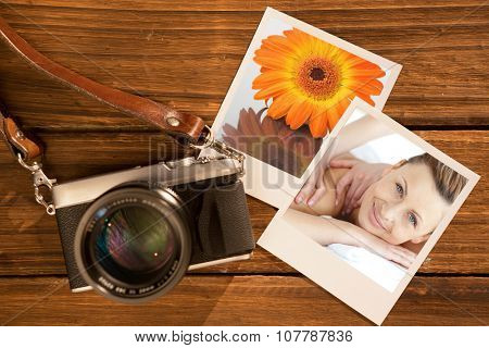 Cheerful woman enjoying a back massage against close up of an orange gerbera on a mirror