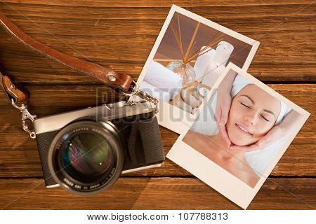 Portrait of a smiling woman having a facial massage against spa objects on wooden floor