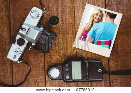 cute boyfriend giving a present against view of an old camera with photo flash