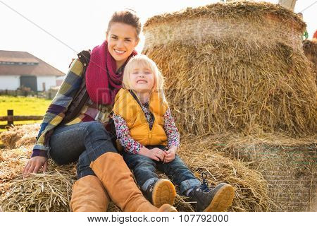 Portrait Of Happy Woman With Cute Child Sitting On Hay On Farm