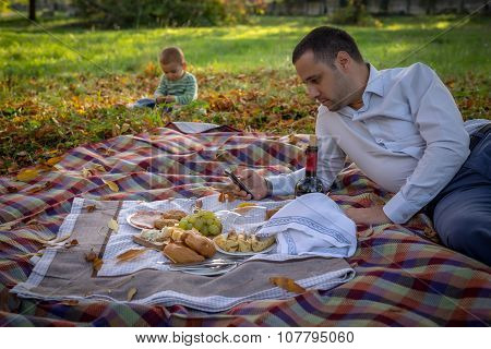 Father And Son Pick-nicking In Autumn Nature