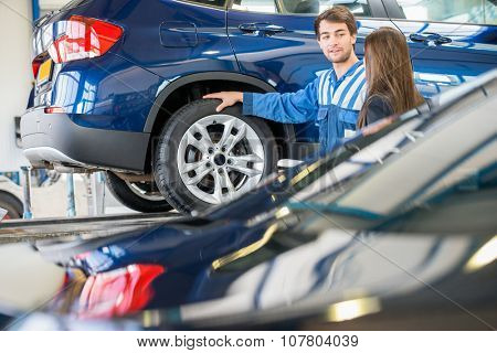 Young mechanic discussing with female customer while standing by car in garage