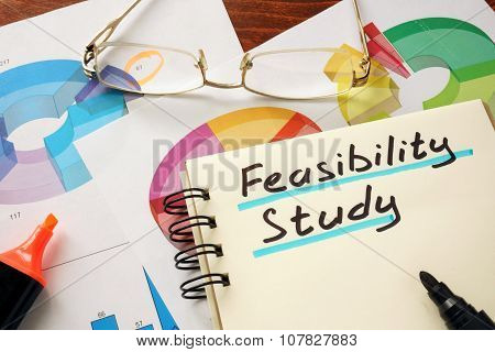 Notepad with feasibility study on a table.