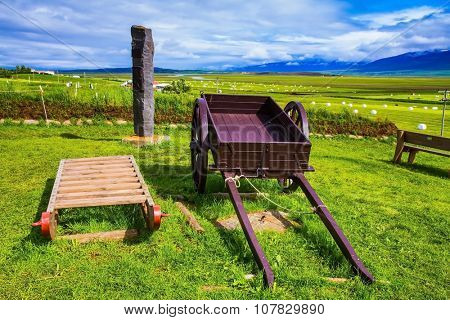 The reconstituted village - Pioneer Museum - Vikings in Iceland. Old wooden sledge and two-wheeled cart on the lawn