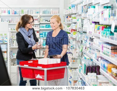 Happy female customer showing product to chemist in pharmacy