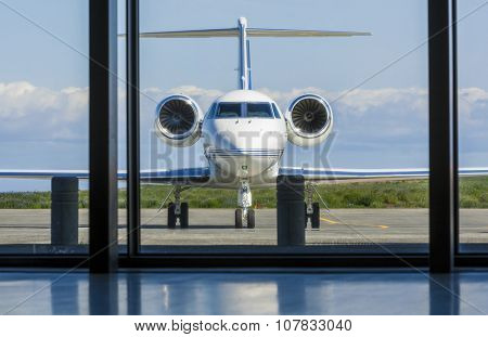Private corporate jet airplane or aeroplane parked at an airport
