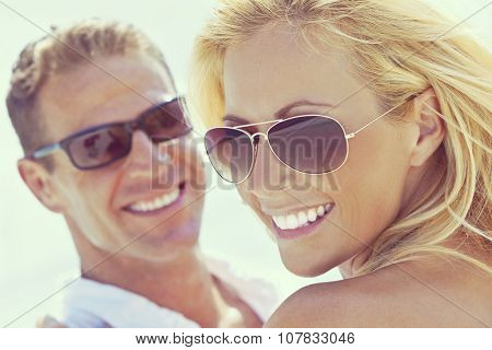 Instagram style photograph of happy and attractive man and woman couple wearing sunglasses and smiling in sunshine at the beach