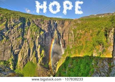 Cloud shaped word of hope in the sky, above a new born rainbow which shines on the waterfall. Concept of new beginning, hope for the earth, hope for the nature, spring beginning , new life. poster