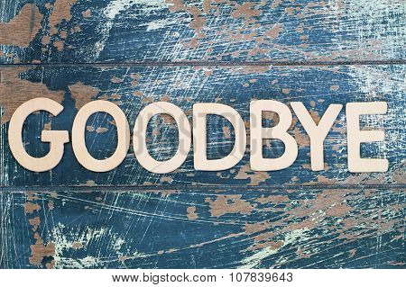 Goodbye written on rustic wooden surface