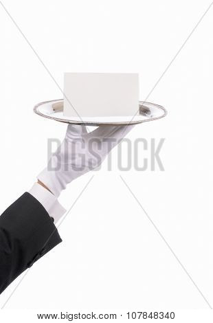 Butlers hand and arm silver serving tray and blank note. Closeup of arm with tuxedo sleeve and formal gloved hand isolated on white.