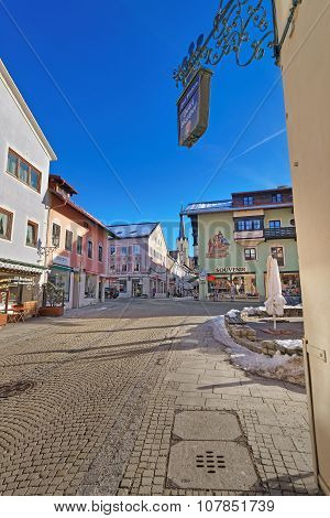 GARMISCH-PARTENKIRCHEN GERMANY - JANUARY 06 2015: Small Bavarian town Garmisch-Partenkirchen with a center filled with painted houses and Maria-Himmelfahrt (Assumption day) church in the background