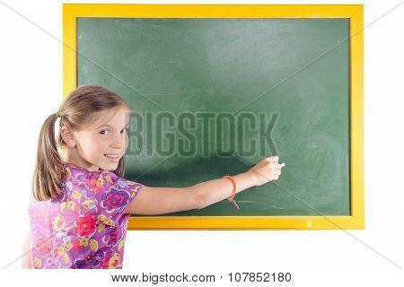 First grade pupil a girl writing on green blackboard