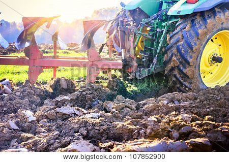 Old Tractor Ploughing Soil In The Agricultural Field